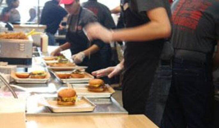 MOOYAH Burgers Fries Shakes Team Members preparing burger orders